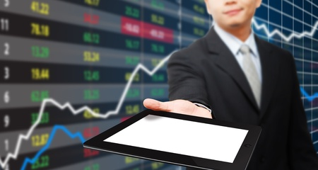 growing business: Smile Business man hold tablet and graph with stock exchange board