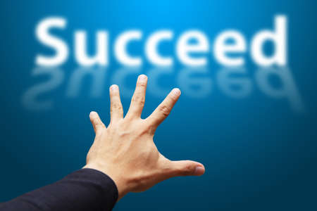 succeed: Hand grab the word Succeed