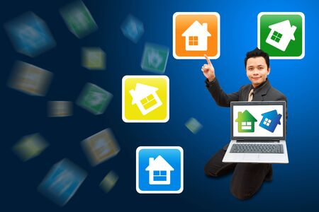 Smile Business man hold notebook computer and point to house icon  Stock Photo - 11801204