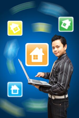 Smile Business man hold notebook computer and point to house icon Stock Photo - 11801255