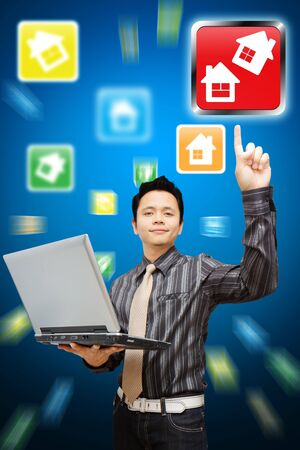 Smile Business man hold notebook computer and point to house icon  Stock Photo - 11801237