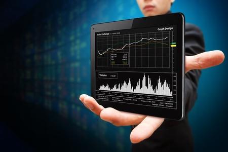 bolsa de valores: El hombre de negocios espera de Tablet PC y el informe de gráfico Foto de archivo