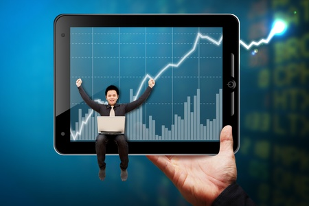 Business man hold Tablet computer and point to graph report  photo
