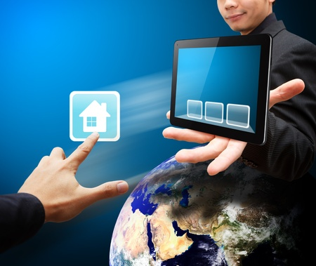 wold map: Business man hold tablet PC and touch on house icon