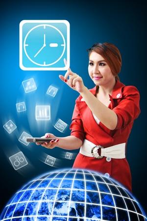 La mujer toca el icono de reloj de un teléfono móvil Foto de archivo