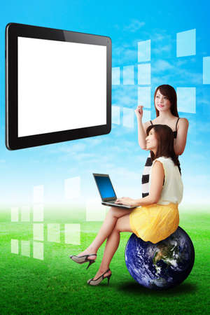 Two lady look at the touch pad on the sky photo
