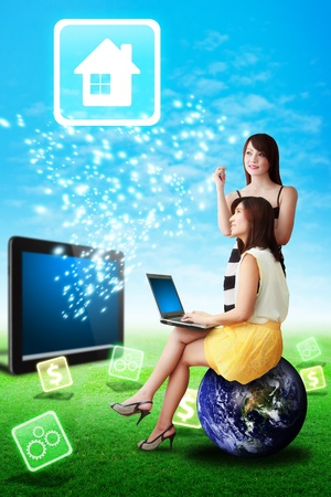Two lady look at the House icon from tablet computer on grass field photo