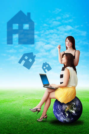 Two lady look at the house icon from notebook computer photo