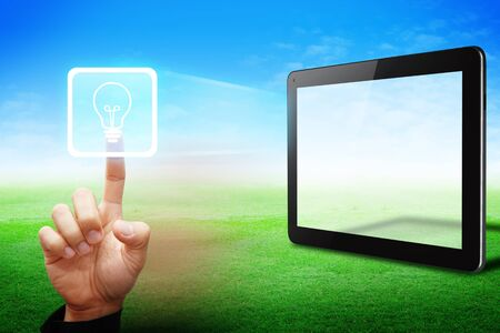 Smart Hand touch on light bulb icon from tablet computer on grass field photo