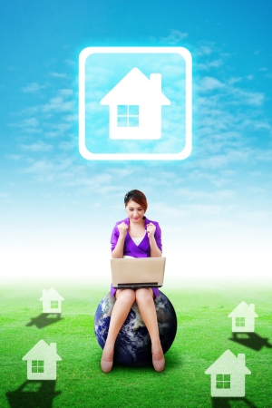 Business woman on grass field and present the House icon