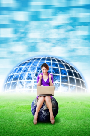 Beautiful woman hold notebook computer and digital world background on the grass field