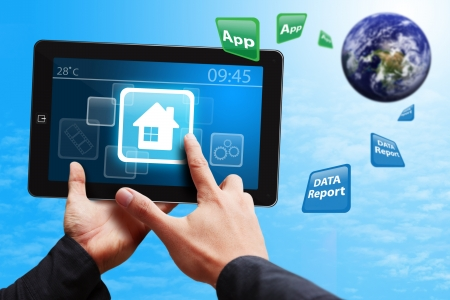 Smart hand press on House icon on tablet pc photo