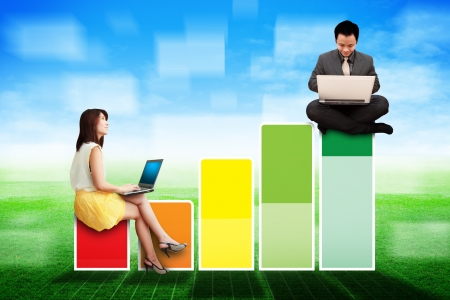 Business man and woman on Bar graph on the grass field  photo