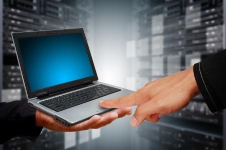 La pressa a mano intelligente sul computer portatile in camera data center
