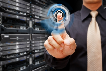 host: Hand press on power button in data center room Stock Photo