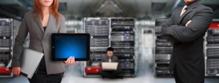 Programmers in data center room and digital tablet for present  Standard-Bild