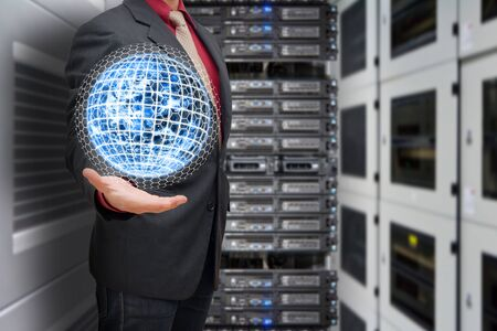 Business man hold the digital earth in data center room photo