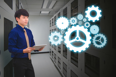 data system: Programmer in data center room with gear system Stock Photo