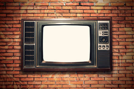 Old vintage TV on the brick wall Imagens
