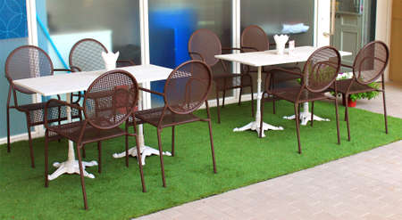Restaurant tables and chairs on cement floor, glasses with tissue papers on the tables  photo