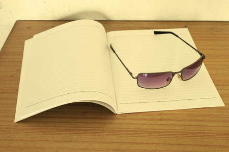 Notebook and sunglasses on the plywood table photo