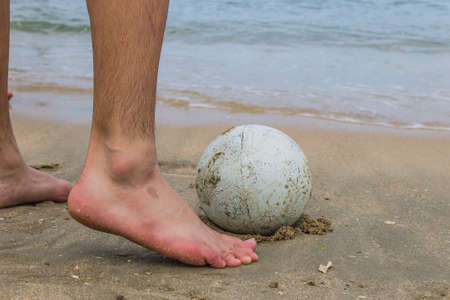 Close-up of male foot playing football on a beach photo
