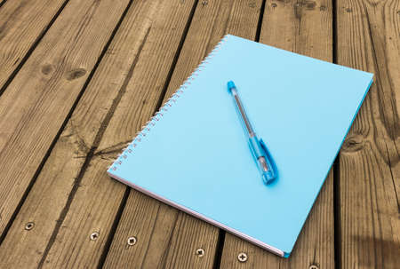 Blue notebook and pen on wood background photo
