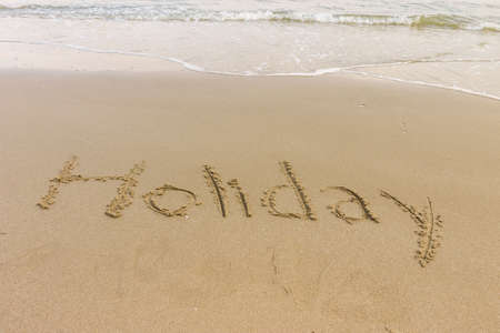 Holiday word written in the sandy beach photo