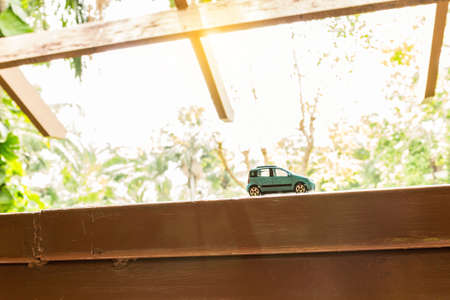 hatchback: Hatchback car toy on wooden terrace with sun light
