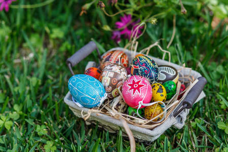 Diverse Easter eggs in a basket, placed on a grass