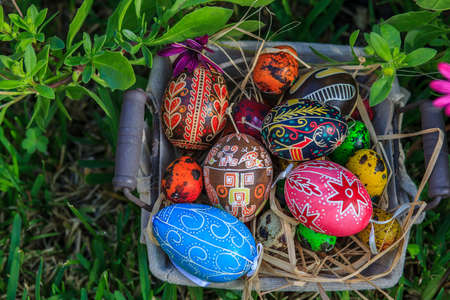 Diverse Easter eggs in a basket, placed on a grass photo