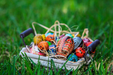 Diverse Easter eggs in a basket, placed on a grass Stock Photo - 18961461