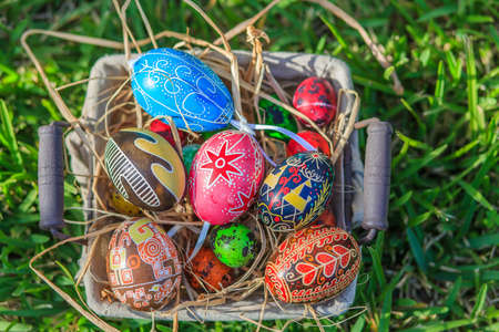 happening: Diverse Easter eggs in a basket, placed on a grass
