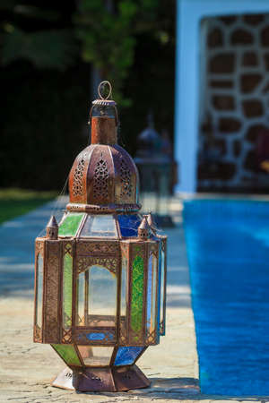 Old rustic lamp wrapped in a spider web, next to the swimming pool