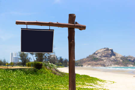 Wooden signboard on the coast with a background of mountains, sea and blue sky Stok Fotoğraf