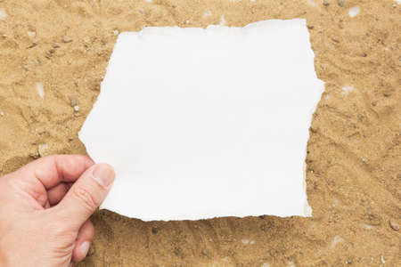 Concept hand holding a blank white paper on a brown sand background,blank paper for your letter. 免版税图像