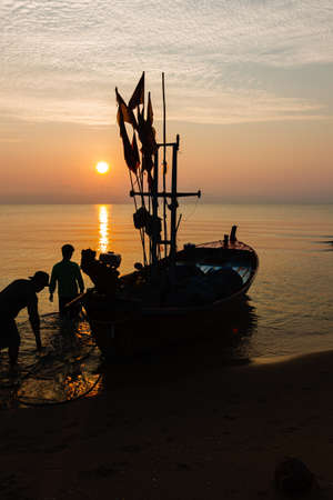 Silhouette of two people on a fishing boat that is about to go fishing in the morning sun.