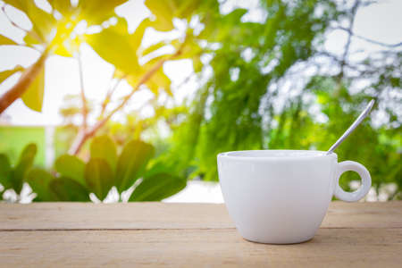 A white coffee cup with spoon is placed on a wooden plate and on the landscape nature background.