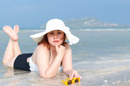 A plump white woman in a bathing suit or swimsuit, white hat, and yellow sunglasses is lying on the beach smiling prone. Stock Photo