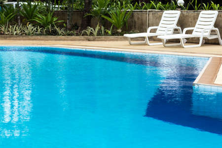 青い水のプールとプールサイドのサンラウン ジャー