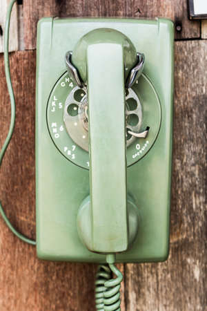 telephonic: close up old green telephone on wood board wall Stock Photo