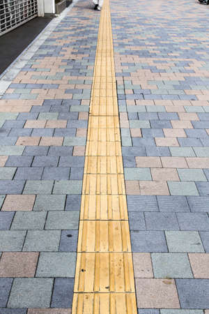braille: the yellow braille block on walkway in japan