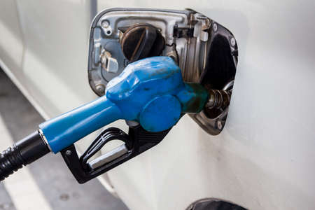 refilling: refilling fuel in the car with dirty blue nozzle at gas station Stock Photo