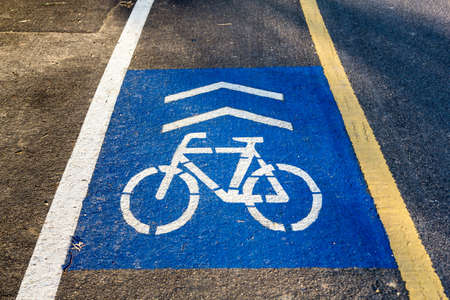 road bike: bike lane sign paint onto blue background on asphalt road