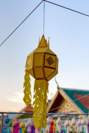 yellow lantern hanging on steel wire rope in thai temple
