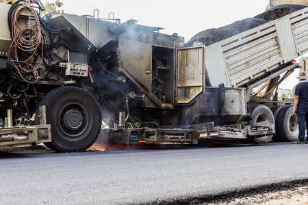 unloading: white truck is unloading asphalt to machine for repair road