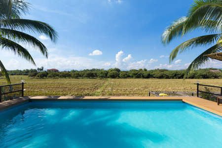 swimming pool with the rice field and blue sky