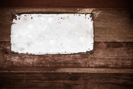 old white metal plate on wooden wall background,vintage tone