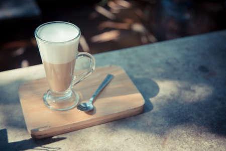 hot latte coffee on wood plate 写真素材