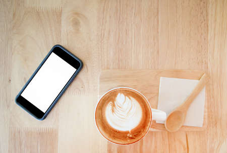 top view of hot coffee and mobile phone on wood table 写真素材